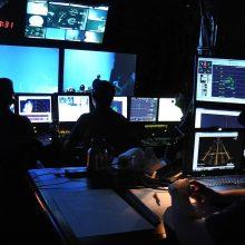 """Tyrimas: specialioje laivo """"Nautilus"""" patalpoje stebimi povandeninių robotų perduodami vaizdai iš jūros dugno."""