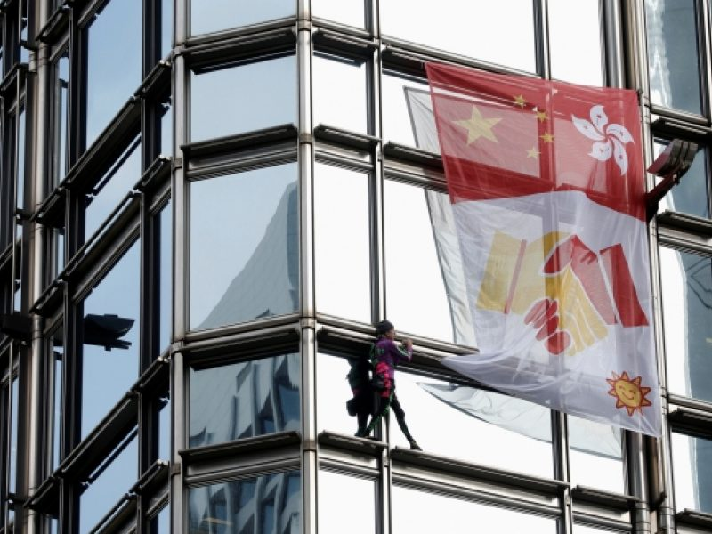 """Prancūzas """"žmogus voras"""" su taikos plakatu užkopė į Honkongo dangoraižį"""